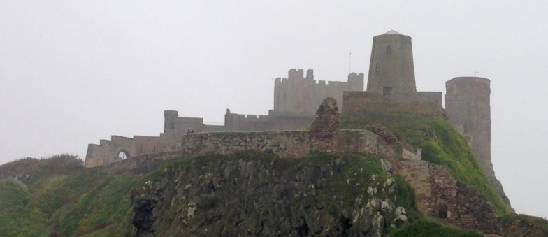Bamburgh Castle shrouded in fog.