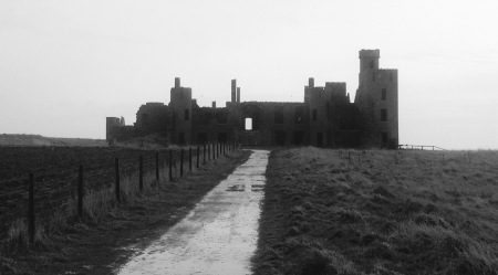 Slains Castle, silhouetted against low mist.