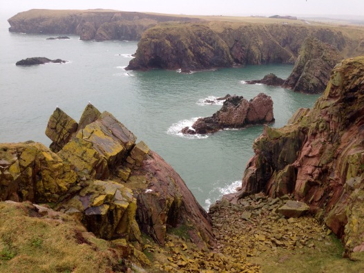 Bays and cliffs of the local deep red Peterhead Granite.