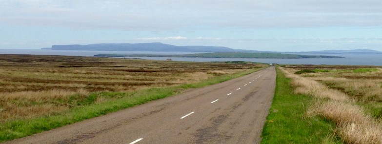 The road to John O'Groats with the Orkneys beyond.